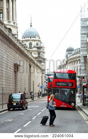 LONDON, UK - JUNE 5 , 2017:  Woman crossing the street in front of red double decker bus still red and therefore remains a widely recognised symbol of the city in London, UK