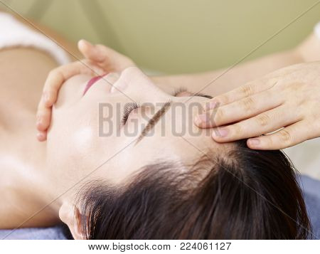 close-up of beautiful young asian woman receiving face massage in spa salon, eyes closed.