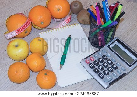Fruits and vitamins with measuring tape. Diet plan. The concept of weight loss, wellness and healthy lifestyle. Vegetarian fruit diet. Products with low fat content