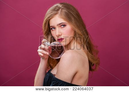 Beautiful portrait of a blonde with a perfume bottle isolated on a plum background