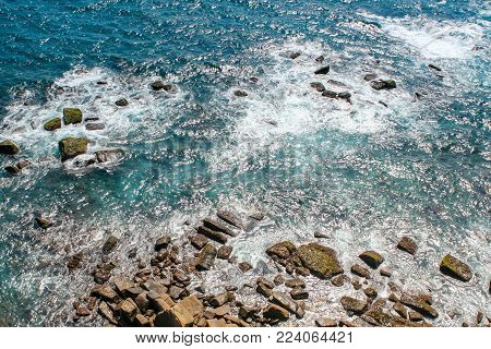 Surf, waves rush into the rocks, top view