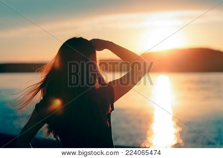 Happy Hopeful Woman Looking at the Sunset by the Sea