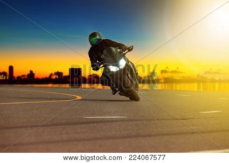 man riding sport motorcycle leaning in sharp curve with traveling scene background