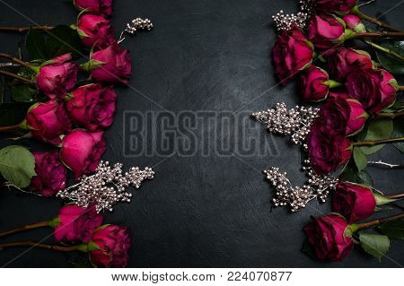 Gothic wedding flowers decor. Dark red or burgundy roses with silver adornment on black background. Bold, daring , alternative , and luxury reception party flower arrangement