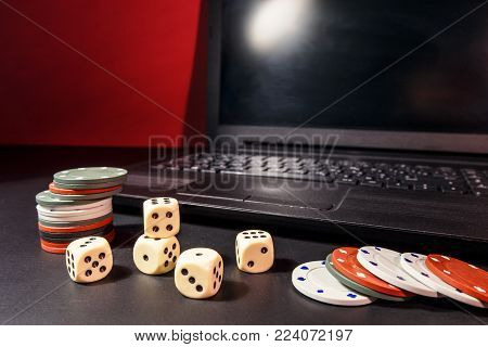 Computer games online concept. Laptop and dice on the table as a symbol of gambling on the Internet.