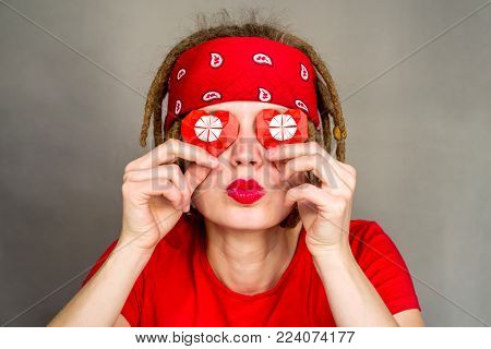 pretty young caucasian hippie woman with afro hair in headband covering eyes with origami paper hearts