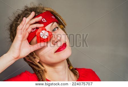 pretty young caucasian hippie woman with afro hairstyle covering eye with origami paper heart and smiling