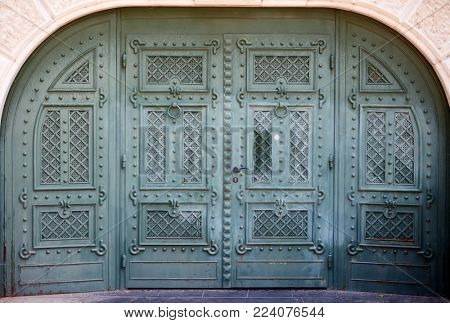 Closeup photo of elegant antique entrance gate of old building.
