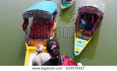 SRINAGAR INDIA - JULY 9 2017 : Lifestyle in Dal lake local people use Shikara a small boat for transportation in Dal lake a famous tourist attraction of Srinagar Jammu and Kashmir state India
