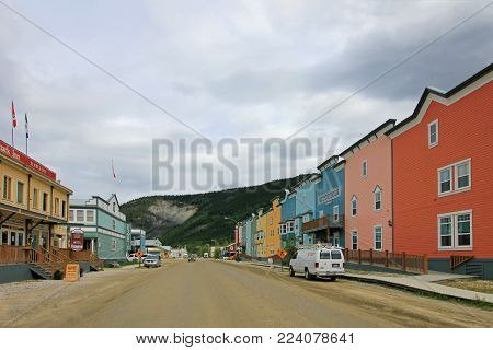 DAWSON CITY, YUKON, CANADA, JUNE 24 2014: Historic buildings and typical traditional wooden houses in a main street in Dawson Citiy on June 24, 2014, Yukon Territory. This legendary city in the north of Canada is a National Historic Site.