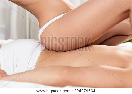 Sexy couple doing erotic massage in bedroom. Woman sitting on man's back. Love and romance concept.