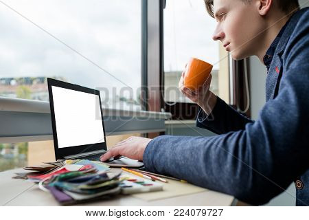Internet browsing. Surfing the web for information. Relaxed designer drinking coffee at his workplace. White screen laptop
