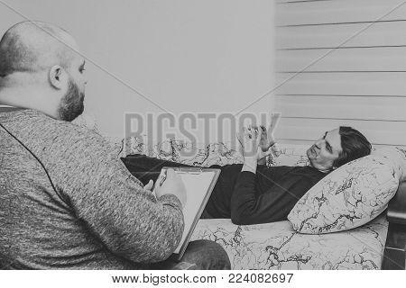 Psychologist consulting session. Patient talking about his problems lying on sofa and psychologist writing down notes, psychotherapy and mental health concept, black and white photo