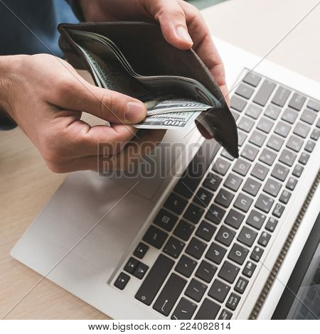 Online casino gambling. Man holding money and placing virtual bets using laptop. Luck success and winning concept poster