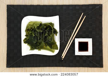 Japanese wakame seaweed food with low sodium soy sauce on porcelain dishes on bamboo background with chopsticks. Has many health benefits and is very high in minerals.