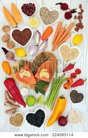 Health food for heart fitness concept with super foods of salmon fish, fruit, vegetables, grain, pulses, seeds, nuts, spice and herbs providing omega 3 fatty acids, anthocyanins and antioxidants.