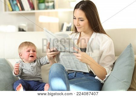 Baby crying demanding attention and his mother ignoring him sitting on a couch in the living room at home