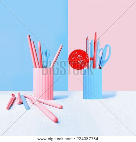 Blue and pink plastic pencil-boxes with pencils, pens, scissors and red round candy against a two-color flat backdrop. Square background with space for copy, selective focus.