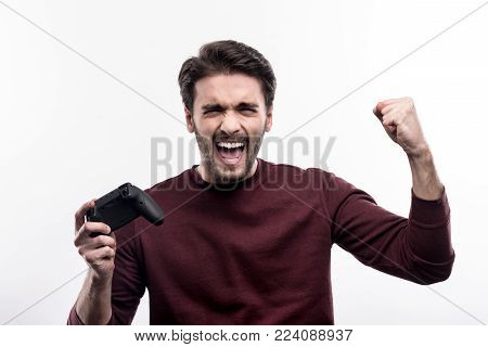 Great victory. Charming joyful man raising his hands in triumph and celebrating the victory in the video game while standing against a white background