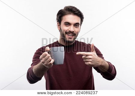Wanna try. Upbeat handsome young man in a burgundy sweater pointing at the cup of coffee and smiling cheerfully while posing isolated on a white background