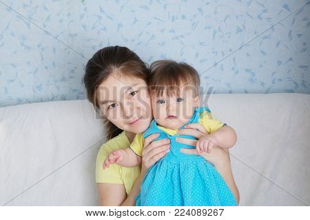 Mother and child portrait, happy smiling woman with  little baby, multinational family with Asian mom and Caucasian daughters, cheerful family