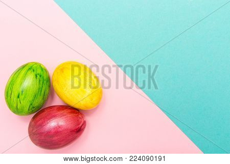 Easter Eggs on turquoise and pink geometric background. Green, yellow and red egg handmade new style of colouring on a colored cardboard. Pattern, easter concept.Flat, top view of egg, geometric background.