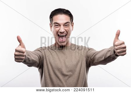 Extremely happy. Upbeat middle-aged man showing thumbs up with both hands, grinning and shouting with joy while standing isolated on the white background