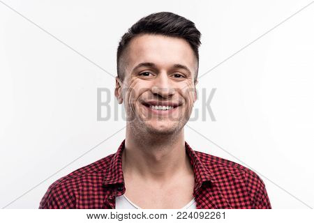 Masculine charms. Handsome upbeat young man with an undercut wearing a checked shirt on top of a t-shirt and smiling at the camera