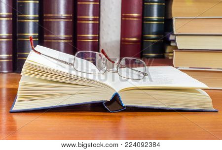 Classic mens eyeglasses lying on the open book in blue hardcover at selective focus with blurred  book text on a wooden table against of the other books