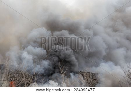 Fire and strong smoke in burning industrial building, danger accident disaster with damage from fire concept