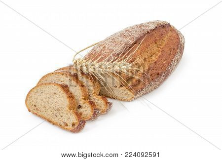 Partly sliced oval loaf of the wheat and rye sprouted bread with added whole sprouted wheat grains, rye malt and molasses and wheat ear beside on a white background