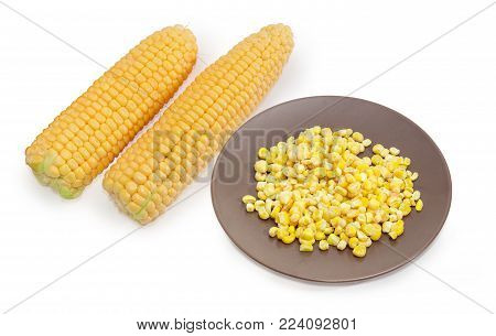 Frozen loose kernels of sweet corn covered with rime on the brown dish against of two ears of the young corn on the cob without green husks on a white background