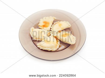 Cooked varenyky - dumplings with sweet filling poured with jam, dish of the Eastern European cuisine on the dark glass dish on a white background