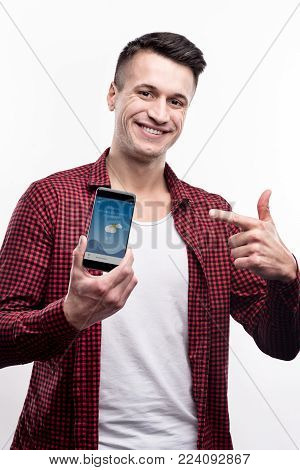 Nice weather soon. Handsome well-built man in a checked shirt pointing at the phone, showing the application with a weather forecast