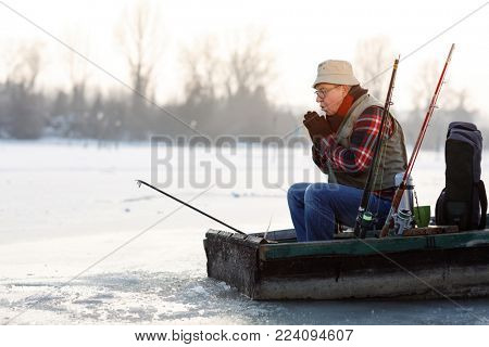 Fisherman in boat worming hands on iced lake