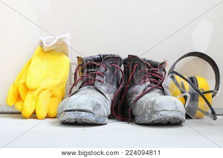 Renovation at home. Construction equipment tools work boots yellow protective noise muffs gloves in building site.