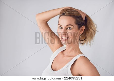 Attractive blond woman holding up her long hair with her hand as she stands smiling at the camera over a neutral studio background with copy space