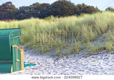 Beach with sand on the German Baltic Sea coast with dunes and woman sunbathing