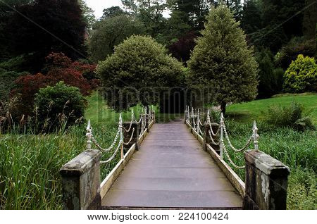 An elegant iron footbridge with decorative chain link railings and stone supports in onramental gardens