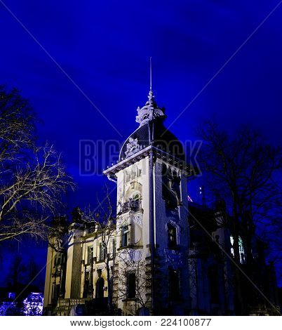 Gloomy haunted house with red and light blue colors illuminated by a street lamp at night