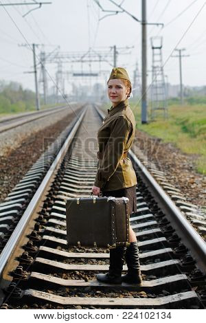 Soviet female soldier with a suitcase in the uniform of the Second World War stands on the train tracks