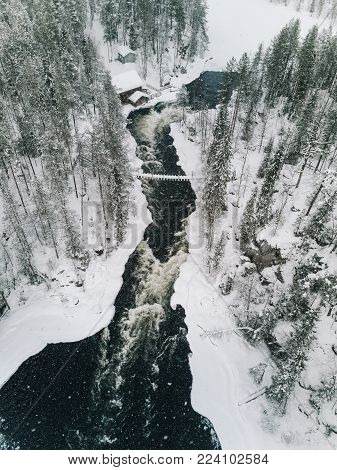 Aerial View Of Icy River Flowing Through A Beautiful Snowy Winter Scenery In Oulanka National Park.