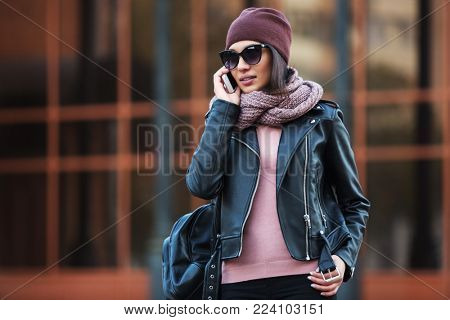 Young fashion woman in black leather jacket using cell phone in city street Stylish female model wearing sunglasses beanie and knitted scarf walking outdoors