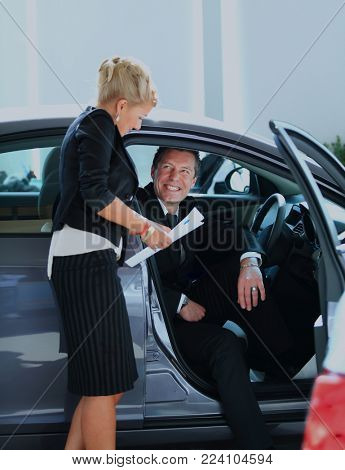 Man buying a car in dealership sitting in his new auto.