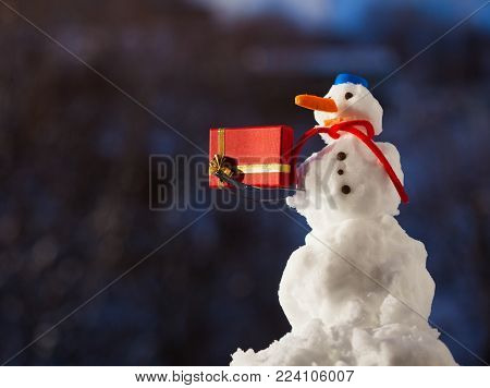 Little happy snowman in blue screw top as hat red scarf and with fork christmas gift box outdoor. Winter season seasonal specific. Blurred background.