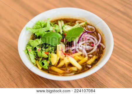 Laksa on wooden table. Laksa is a spicy noodle soup popular in the Peranakan cuisine.