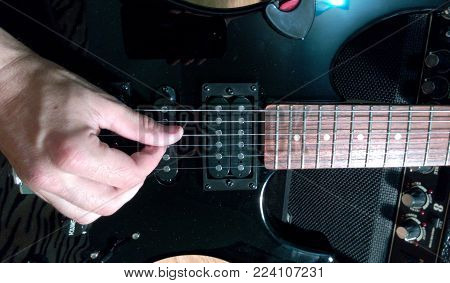 Playing the electric guitar with your fingers style black stratocaster