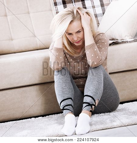 Depression. Middle aged barefoot woman sitting at the floor embracing her knees, near sofa at home, her head down, bored, troubled with domestic violence.