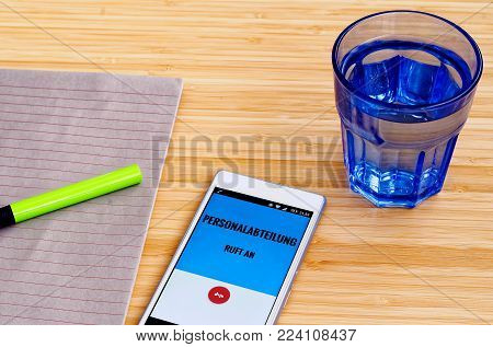 Mobile phone at which the human resources department calls and in German language HR department calls stands (in English: Mobile phone at which the person) with block and green pen and tumbler