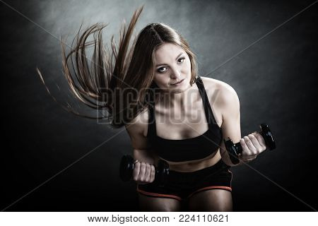 Fitness girl fit woman lifting dumbbells weights doing exercise with dumb bells training shoulder muscles motion wind blowing hair gray background